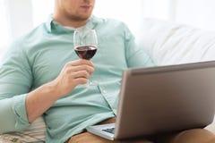Feche acima do homem com vidro do portátil e de vinho Fotografia de Stock Royalty Free
