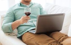 Feche acima do homem com vidro do portátil e de vinho Foto de Stock Royalty Free