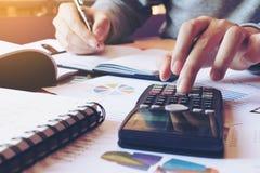 Feche acima do homem da mão que faz a finança e calcule na mesa sobre o custo foto de stock