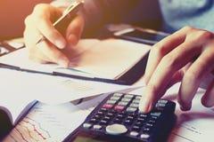 Feche acima do homem da mão que faz a finança e calcule sobre o custo com th imagem de stock royalty free