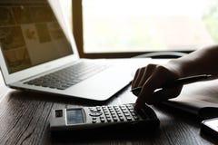 Feche acima do homem da mão que faz finanças e calcule na mesa sobre o escritório do custo em casa Economias, finanças e conceito imagem de stock royalty free