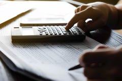 Feche acima do homem da mão que faz finanças e calcule na mesa sobre o escritório do custo em casa Economias, finanças e conceito imagem de stock