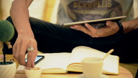 Feche acima do homem da mão que usa a tabuleta no café do café na tabela, vídeos de arquivo