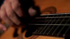 Feche acima do homem das mãos que joga a música na guitarra acústica das cordas vídeos de arquivo