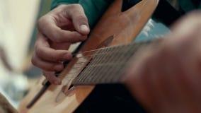 Feche acima do homem das mãos que joga a música na guitarra acústica das cordas video estoque