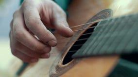 Feche acima do homem das mãos que joga a música na guitarra acústica das cordas filme