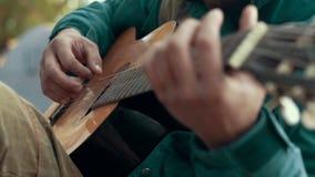 Feche acima do homem das mãos que joga a música na guitarra das cordas filme