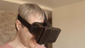Feche acima do homem de cabelo cinzento que tem o divertimento usando seus auriculares do telefone celular VR em casa Máscara da  vídeos de arquivo