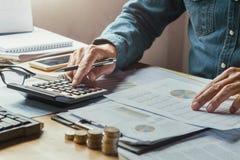 feche acima do homem de negócio da mão que usa a calculadora para calcular dos dados Imagem de Stock