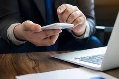 Feche acima do homem de negócio novo que usa o telefone esperto móvel para o trabalho foto de stock royalty free