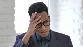 Feche acima do homem de negócios africano Stressed com funcionamento da dor de cabeça no portátil vídeos de arquivo