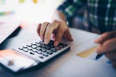 Feche acima do homem de negócios ou do contador que trabalham na calculadora para calcular dados comerciais, e do documento da co fotografia de stock