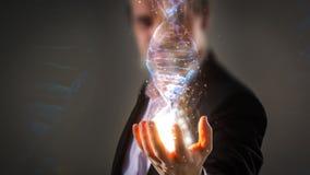 Feche acima do homem de negócios que guarda a hélice de incandescência do ADN com sp da energia fotografia de stock royalty free