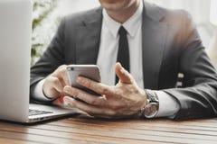 Feche acima do homem de negócios que olha a tela do telefone celular no café da rua imagens de stock royalty free