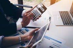 Feche acima do homem de negócios que trabalha na calculadora para calcular dados comerciais o relatório financeiro na sala de reu imagens de stock royalty free