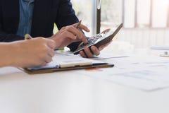 Feche acima do homem de negócios que trabalha na calculadora para calcular dados comerciais o relatório financeiro na sala de reu foto de stock