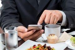 Feche acima do homem de negócios que verifica a notícia do telefone celular fotografia de stock royalty free