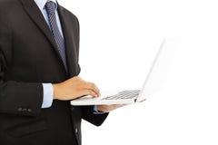 Feche acima do homem de negócios usando o portátil à disposição Imagem de Stock