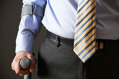 Feche acima do homem de negócios Using Crutch Foto de Stock