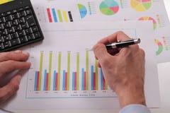 Feche acima do homem de negócios que trabalha em dados financeiros no formulário das cartas e dos diagramas Estatísticas de negóc Foto de Stock