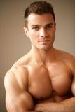Feche acima do homem desportivo com os braços musculares cruzados Imagem de Stock