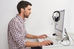 Feche acima do homem farpado concentrado bonito novo na camisa quadriculado que senta-se na tabela na sala clara, jogando jogos Imagens de Stock Royalty Free