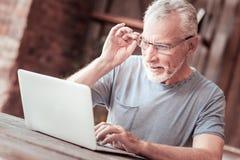 Feche acima do homem idoso com um portátil imagens de stock royalty free
