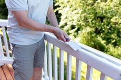 Feche acima do homem maduro que raspa a pintura velha da plataforma exterior fotografia de stock royalty free