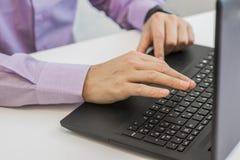 Feche acima do homem a multitarefas das mãos que usa o Internet de conexão do portátil Imagem de Stock Royalty Free
