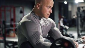 Feche acima do homem muscular no treinamento do sportswear no gym com um barbell que faz o exercício do bíceps filme