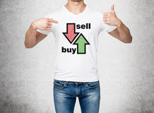 Feche acima do homem nas sarjas de Nimes e de um t-shirt branco que indicam à caixa com setas tiradas: compre e venda O conceito  Imagens de Stock