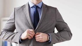 Feche acima do homem no botão da asseguração do terno no revestimento vídeos de arquivo