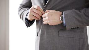 Feche acima do homem no botão da asseguração do terno no revestimento video estoque