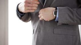 Feche acima do homem no botão da asseguração do terno no revestimento filme