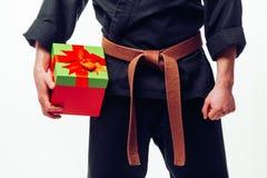Feche acima do homem novo com treinamento alaranjado do lutador do karaté da correia com caixa de presente Foto de Stock Royalty Free