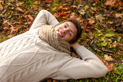 Feche acima do homem novo de sorriso que encontra-se no parque do outono Fotografia de Stock