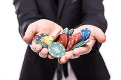 Feche acima do homem novo no terno que sustenta microplaquetas de pôquer da vitória no jogo Fotografia de Stock Royalty Free
