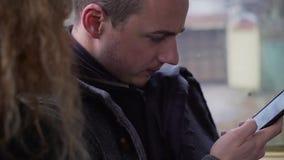 Feche acima do homem novo que consulta meios sociais no telefone celular durante comutam video estoque