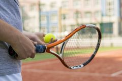 Feche acima do homem novo que guarda a bola e a raquete de tênis fotos de stock royalty free