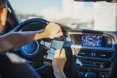 Feche acima do homem novo que olha o navegador de GPS atrás da roda no carro foto de stock
