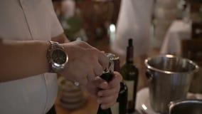 Feche acima do homem que as mãos abrem uma garrafa do vinho filme