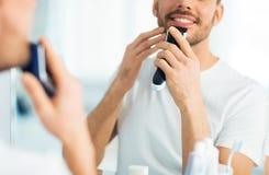 Feche acima do homem que barbeia a barba com ajustador fotos de stock royalty free