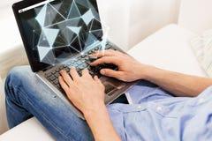 Feche acima do homem que datilografa no laptop em casa Imagens de Stock