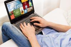 Feche acima do homem que datilografa no laptop em casa Fotos de Stock