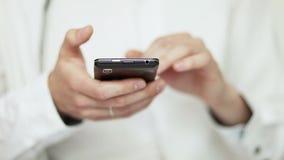 Feche acima do homem que datilografa no telefone celular do touchpad vídeos de arquivo