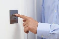 Feche acima do homem que desliga o interruptor da luz foto de stock
