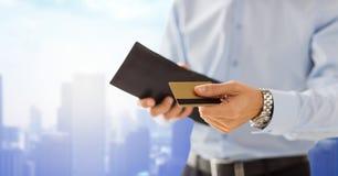 Feche acima do homem que guarda a carteira e o cartão de crédito Fotografia de Stock
