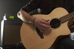 Feche acima do homem que joga a guitarra acústica amplificada Fotografia de Stock Royalty Free