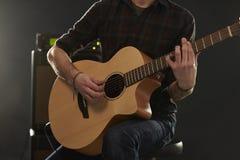 Feche acima do homem que joga a guitarra acústica amplificada Foto de Stock