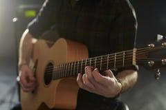 Feche acima do homem que joga a guitarra acústica no estúdio Imagens de Stock